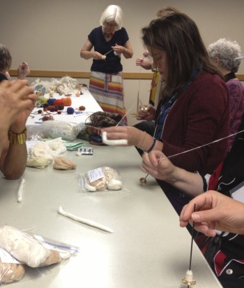 Selina learning to spin cotton with a Tahkli drop spindle at the 2013 WARP Meeting