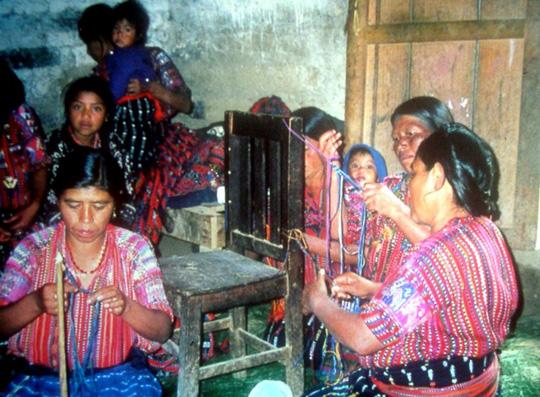 Village of Morales, Guatemala.  Making macrame friendship bracelets.